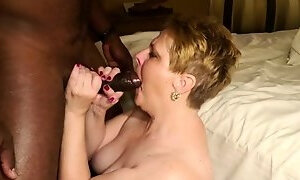 Buxom mature blonde milks a big black shaft with her mouth
